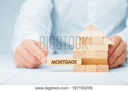 Mortgage concept. Financial agent complete wooden model of the house with last piece with text mortgage.