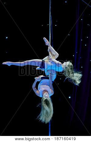 MOSCOW, RUSSIA - FEB 11, 2017: Female duet participants perform on stage of Korolevskiy concert hall during Pole Dance Show. Concert hall is designed for 750 spectators.