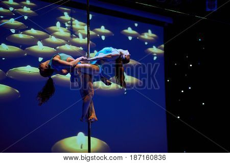 MOSCOW, RUSSIA - FEB 11, 2017: Female duet performs against background with burning candles on stage of Korolevskiy concert hall during Pole Dance Show. Concert hall is designed for 750 spectators.