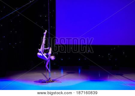 MOSCOW, RUSSIA - FEB 11, 2017: Female participant of Pole Dance Show performs on stage in Korolevskiy concert hall. Concert hall is designed for 750 spectators.