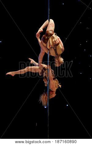 MOSCOW, RUSSIA - FEB 11, 2017: Female duet performs on stage of Korolevskiy concert hall during Pole Dance Show. Concert hall is designed for 750 spectators.