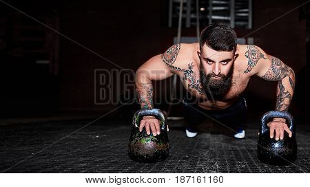 Strong handsome bearded man doing push-ups on dumbbells in a gym as bodybuilding exercise training his muscles. Young muscular man training with kettle bell