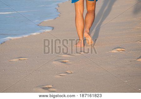 Closeup of a man's bare feet walking at a beach at sunset