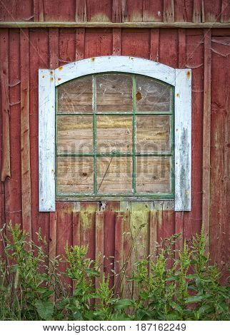 A boarded up broken window of a classic red countryside barn.