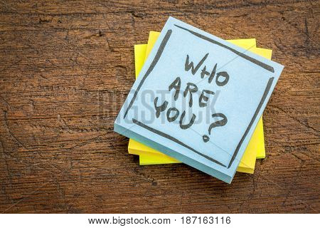 Who are you question - handwriting on a sticky note against rustic wood board