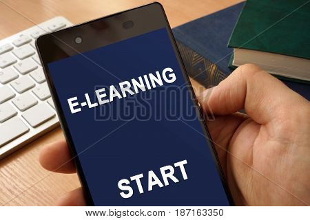 Hand with smartphone  and app E-learning. Distance education concept.