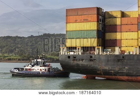 container ship being pushed by a tugboat in Panama canal