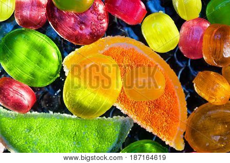 Delicious background, multicolored lollipops and slices of marmalade , top view