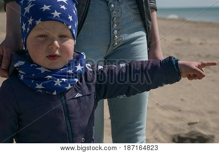 Little boy about three years old next to mom showing thumb to the right in the spring on the beach