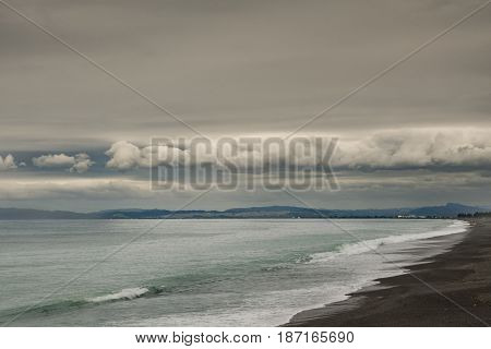 Napier New Zealand - March 9 2017: South side of Hawkes Bay with black lava beach and surf in front all under heavy dark storm clouds cut by band of white clouds. Shine on Pacific Ocean water.