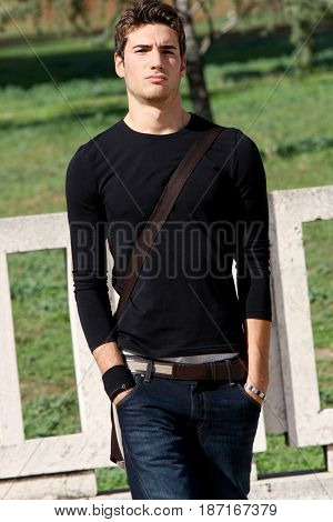 Fashionable and handsome young man outdoors. Wearing a casual clothes, black long sleeved t-shirt and jeans. Modern hairstyle. Behind him a park. Serious and confident look, hands in pockets.