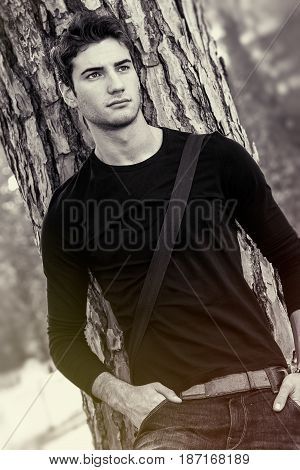 Portrait of a young and handsome man outdoors leaning on a trunk of a tree. Intense and sensual look. Charming and attractive. The boy wears simple clothes. Hands in his pockets. Black and white.