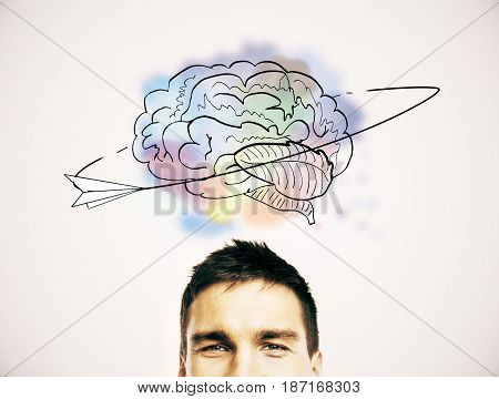 Half portrait of cheerul young european man with creative brain sketch above head. Brainstorm concept