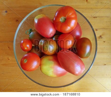 Ripe and unripe tomatos in the bowl at the wooden table.