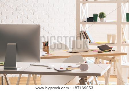 Modern office interior with gadget supplies and coffee cup on table