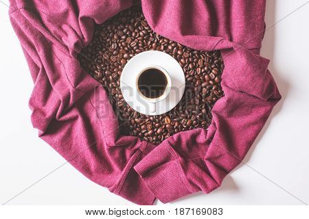 Coffee cup and beans surrounded with shirt sleeves