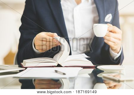 Businessman drinking coffee and reading book at workplace/in modern office. Close up Education concept