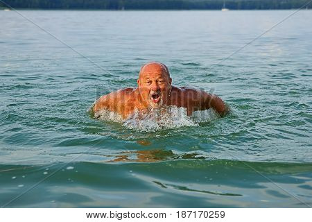 Swimmer Senior man swimming butterfly strokes. Caucasian male aged 60 years