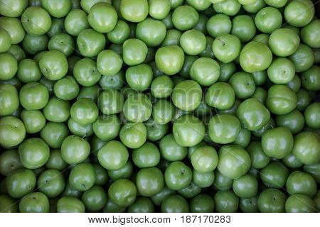 A box of Greengage plums fruits for sale in a vegetable shop. Greengage plums background. Horizontal. Top view.