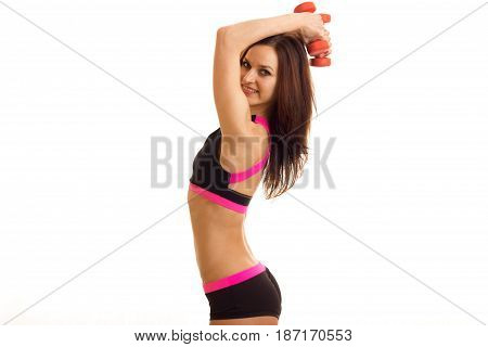 charming slender girl stands before the camera sideways and raise the dumbbells above your head isolated on white background