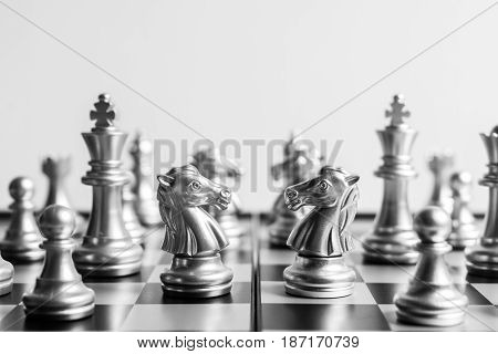 Abstract chess knights face to face on a chessboard in black and white