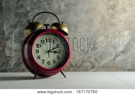 Bare cement wall background with retro alarm clock on table