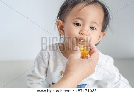 Asian little girl takes medicine syrup with her mother