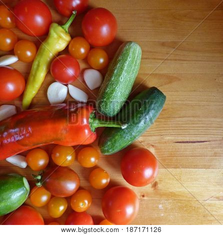 Vegetable background. Red ripe tomatoes, cherry, cucumbers, garlic and peppers in wooden table. Fresh organic products, pure eco food. Rural still life - new vegetables harvest. With place for text.