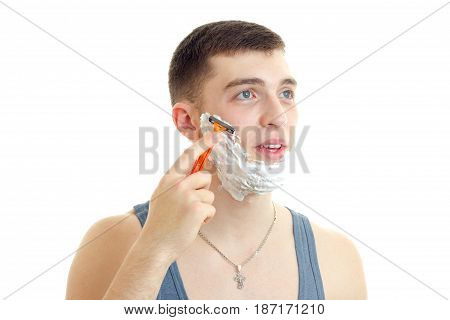 Portrait of a handsome young guy with foam on his face that opened the mouth looks up and shaves his beard is isolated on a white background.