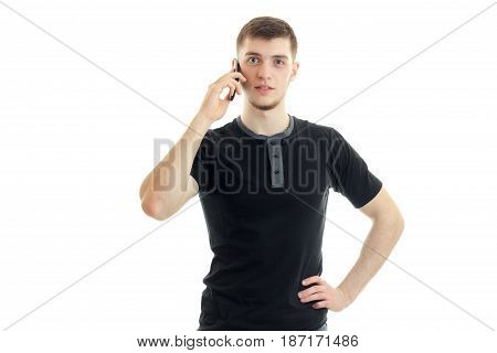 a charming young man in a black t-shirt looks straight and keeps a mobile phone near your ear is isolated on a white background