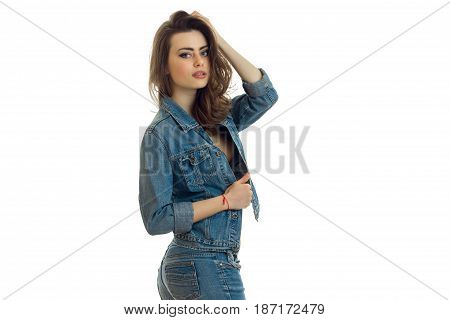 sexy young girl in jeans suit stands sideways and posing for the camera isolated on white background