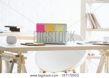 Back view of open laptop with sticker placed on modern office workplace with coffee cup supplies and other items