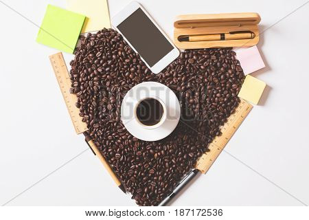 Top view of coffee cup beans shaped as a heart supplies and blank smartphone. Morning concept