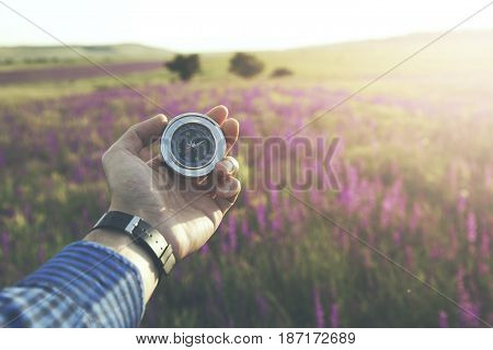 Hand man holding compass navigator on road way