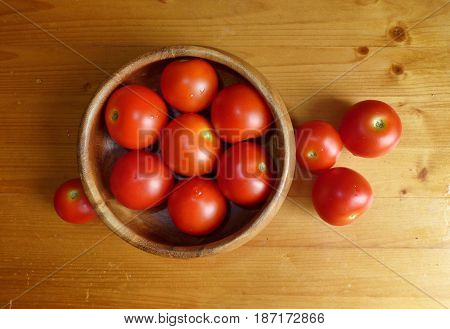 Ripe red tomatoes in the bowl and near it at the wooden table.  Fresh organic products, pure eco food. Rural still life - new vegetables harvest.