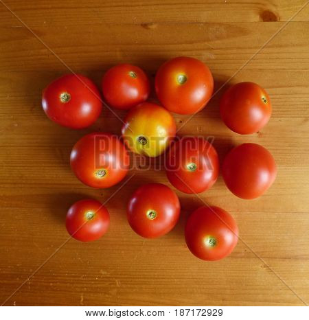Red ripe tomatoes and cherry at the wooden table. Vegetable background.  Fresh organic products, pure eco food. Rural still life - new vegetables harvest.