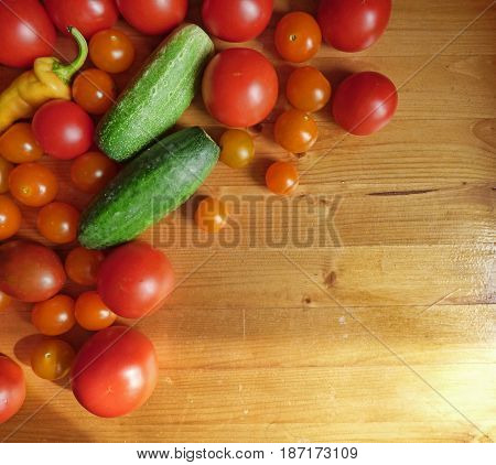 Red ripe tomatoes, cherry, cucumbers and peppers in wooden table. Vegetable background. Fresh organic products, pure eco food. Rural still life, top view. With place for text.