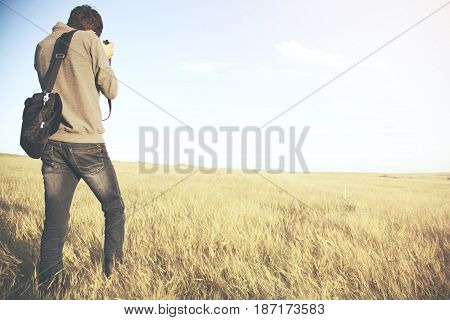 Young man photographer on a field at morning
