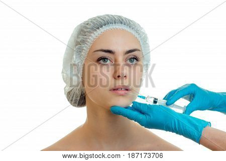 Portrait of a young girl in a medical CAP which the doctor injects the vaccine on the face with gloved hands isolated on white background