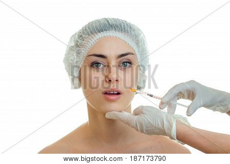 Portrait of a young girl without makeup in a special hat which the surgeon makes injection isolated on white background