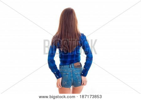 a young girl with long hair in a blue shirt and denim shorts worth turning your back to the camera and keep your hands on your hips isolated on white background.