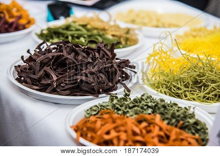 Assorted bundles of colorful raw pasta noodles.
