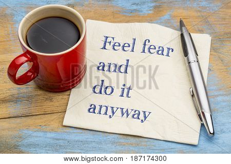 Feel fear and do it anyway - inspiration handwriting on a napkin with coffee