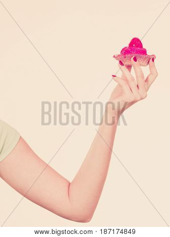 Sweets fat food sugar concept. Woman hand holding sweet strawberry cupcake