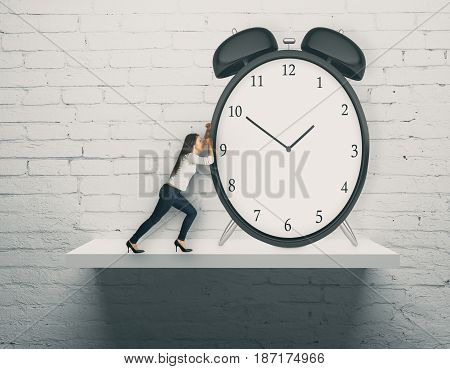 Abstract image of young woman pushing huge alarm clock placed on white shelf. Brick wall background. Time management concept. 3D Rendering