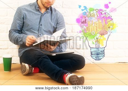 Businessman reading book while sitting on wooden floor with coffee cup and lamp sketch. Brick wall background. Idea concept