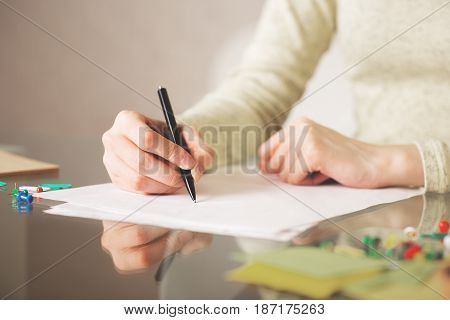 Close up of female hands writing on paper sheets placed on glass desk with colorful supplies and other items. Paperwork concept
