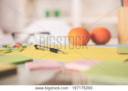 Close up of blurry workplace with oranges supplies glasses and other items