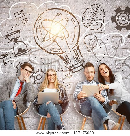 Cheerful young team sitting on chairs and using laptops on concrete background with creative drawings. Idea concept