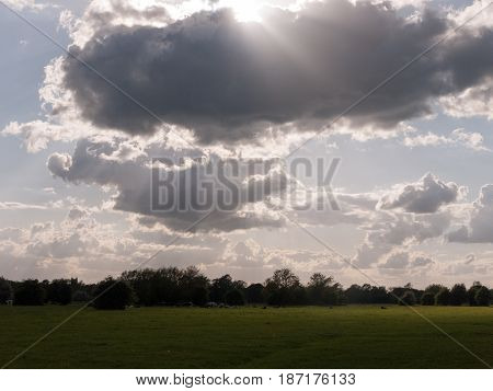The Sun Poking Through With Beams Of A Very Cloudy Sky Above An Open Country Scene Outside In Essex